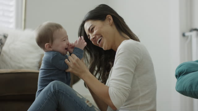 stockvideo's en b-roll-footage met medium shot of mother sitting on floor clapping hands with son / provo, utah, united states - provo
