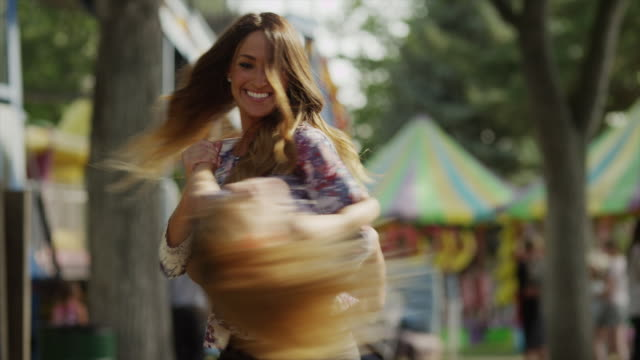 Medium shot of mother spinning daughter at carnival / American Fork, Utah, United States