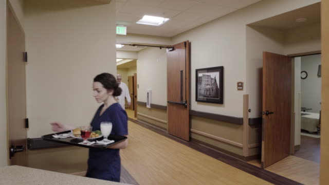 Medium shot of nurse taking food into a room