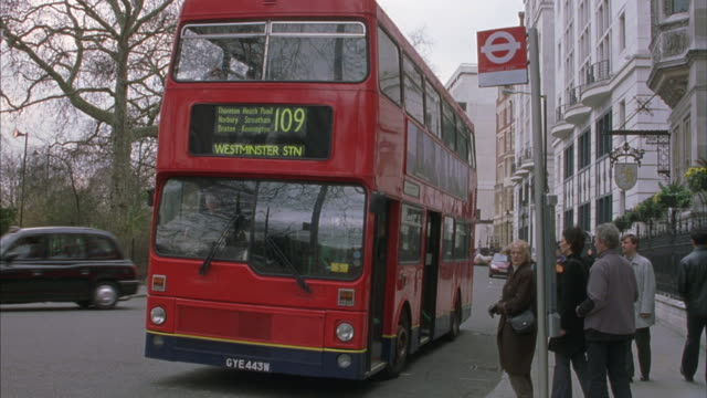 Medium shot of one of London's famous double decker buses at a bus stop.