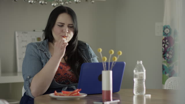 Medium shot of overweight woman eating snack and using laptop / Orem, Utah, United States