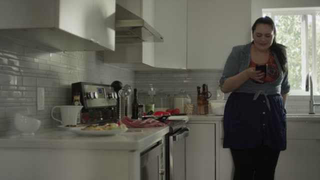 Medium shot of overweight woman in kitchen texting on cell phone / Orem, Utah, United States