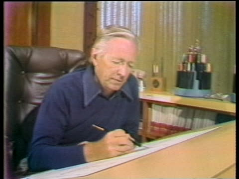 medium shot of peanuts creator charles schulz seated at drawing board drawing his comic strip. schulz is the legendary artist who created such... - カトゥーニスト点の映像素材/bロール