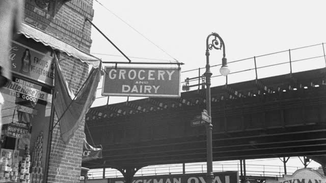 vidéos et rushes de medium shot of pedestrians walking by grocery store with elevated subway track in background, new york city, new york state, usa - 1930