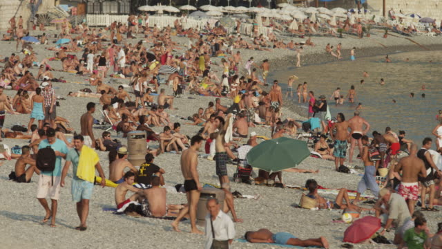 Medium shot of people enjoying French beach / Nice, France