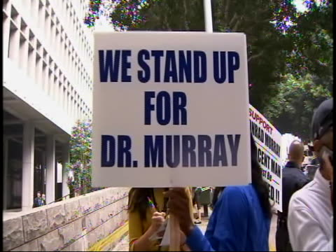 medium shot of people rallying in support of dr conrad murray who was accused of involuntary murder of the pop music icon murray pleaded not guilty... - prison icon stock videos & royalty-free footage