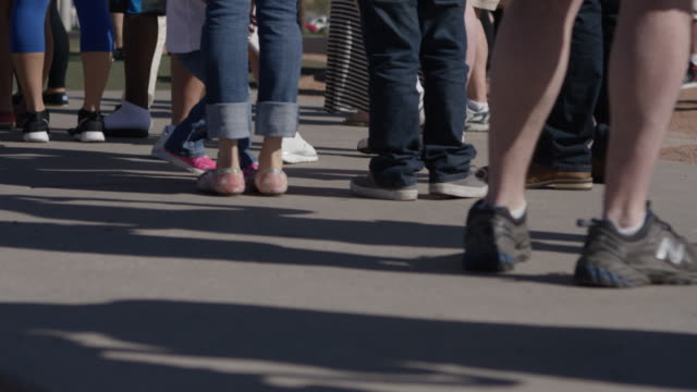 a medium shot of people standing in line - aspettare video stock e b–roll