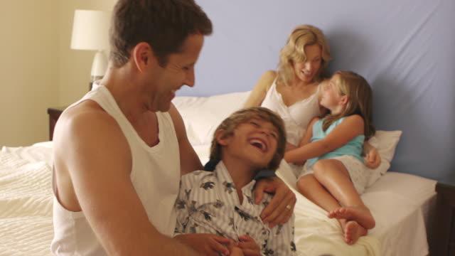 Medium shot of playful family in bedroom/Marbella region, Spain