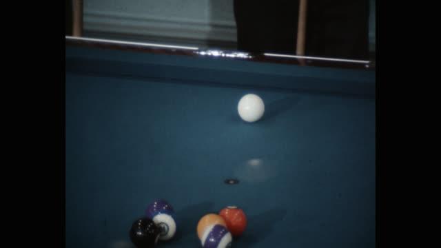 medium shot of pool table with balls, man standing near - キューボール点の映像素材/bロール