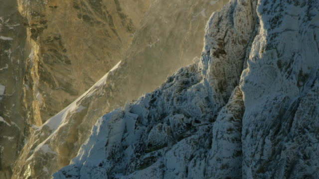 medium shot of powder snow whirling at a cliff of the teton range at sunrise - steep stock videos & royalty-free footage