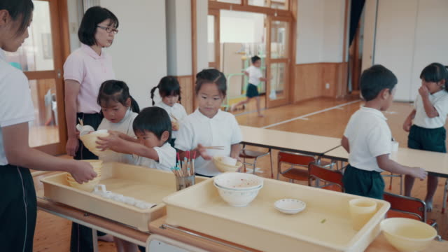 Medium shot of preschool students cleaning up after lunch