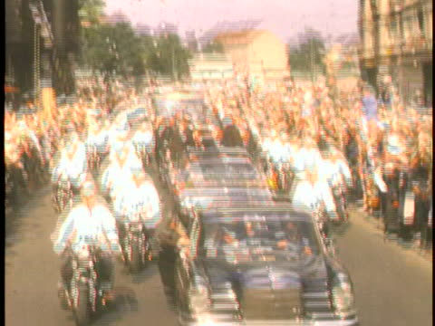 medium shot of president john f. kennedy in a presidential motorcade on the right of the screen, and a huge crowd of people gathered to see him on... - john f. kennedy us president stock videos & royalty-free footage
