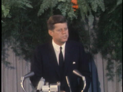 medium shot of president john f. kennedy standing at a lectern with several microphones before him. he is wearing a dark suit and dark tie, and... - see other clips from this shoot 1900 video stock e b–roll