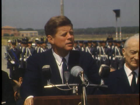 medium shot of president john f. kennedy walking across the tarmac at an airport towards a podium. the tarmac has been decorated in honor of... - john f. kennedy us president stock videos & royalty-free footage