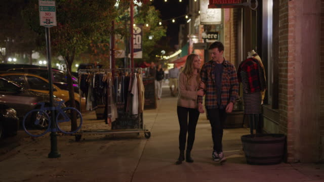 stockvideo's en b-roll-footage met medium shot of romantic couple walking in city at night / provo, utah, united states - provo
