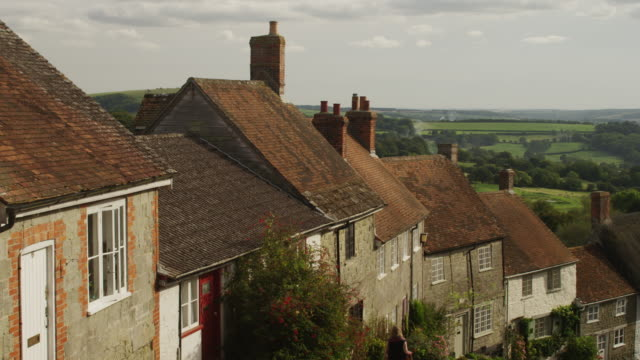 Medium shot of rowhouses in English village / Gold Hill, Shaftsbury, England, United Kingdom