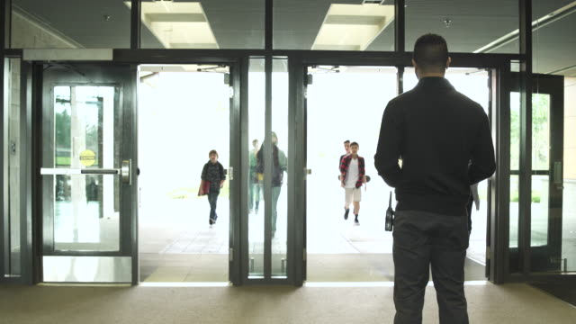 Medium shot of security person standing while students enter from front door