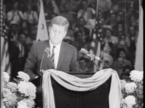 medium shot of senator john f. kennedy, wearing a dark suit and tie, standing at a well-decorated lectern. there is a large crowd and american flags... - ジョン・f・ケネディ点の映像素材/bロール