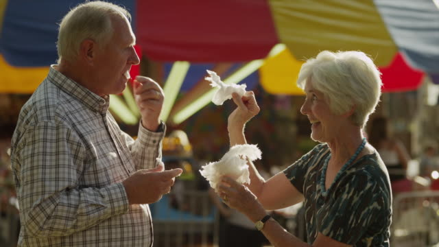 medium shot of senior couple feeding each other cotton candy at carnival / american fork, utah, united states - senior couple stock videos & royalty-free footage