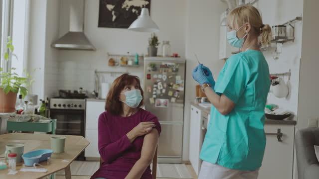 vidéos et rushes de projectile moyen de patient féminin aîné obtenant le vaccin covid-19 tiré à la maison - large