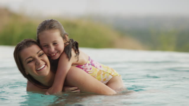 medium shot of sisters playing in infinity pool / cedar hills, utah, united states - piggyback stock videos & royalty-free footage
