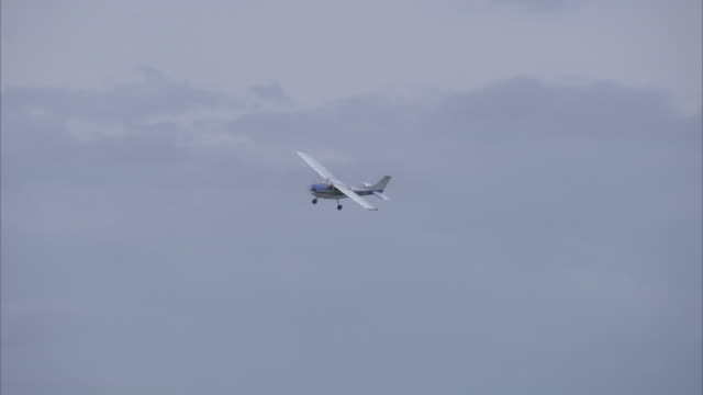 vidéos et rushes de medium shot of small motor plane flying in the sky - propeller