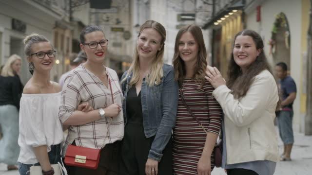 vídeos de stock, filmes e b-roll de medium shot of smiling women posing in city / salzburg, austria - jaqueta jeans