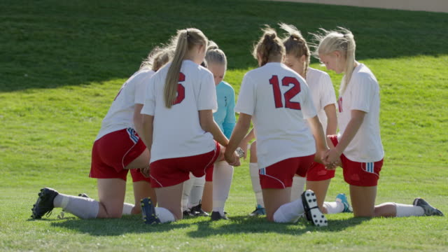 medium shot of soccer players praying / springville, utah, united states - springville utah stock videos & royalty-free footage