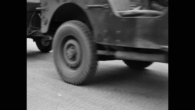 medium shot of soldier walking with cardboard box behind jeep driving on dock - korean war - korea stock videos & royalty-free footage