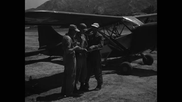 medium shot of soldiers talking, standing by cessna prop airplane at airfield - four people stock videos & royalty-free footage