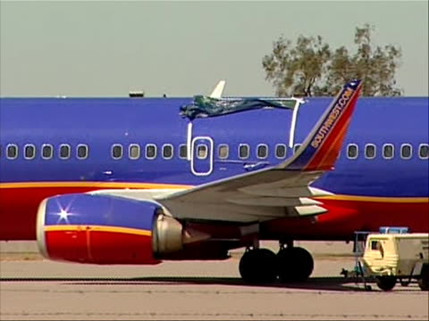 medium shot of southwest plane that made an emergency landing in yuma, arizona on april 1, 2011 due to structural problems. this caused the national... - südwesten stock-videos und b-roll-filmmaterial