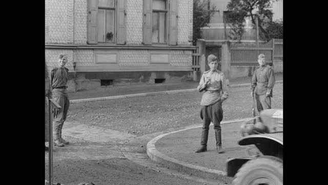 medium shot of soviet soldiers watching us army vehicles driving on street, post wwii germany - postwar stock videos & royalty-free footage