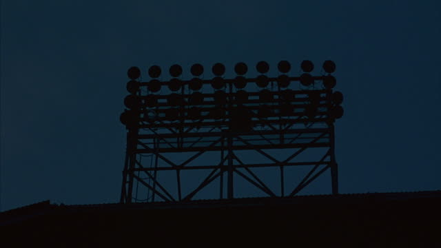 Medium shot of stadium lights turning on.