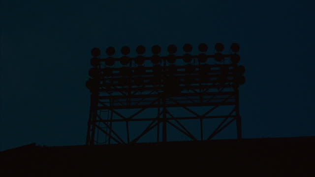 medium shot of stadium lights turning on. - floodlight stock videos & royalty-free footage