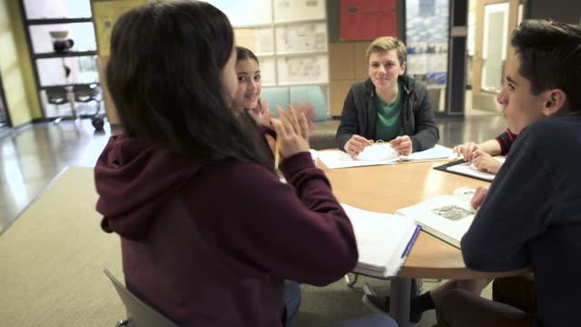 medium shot of student sitting around a table - högstadium bildbanksvideor och videomaterial från bakom kulisserna