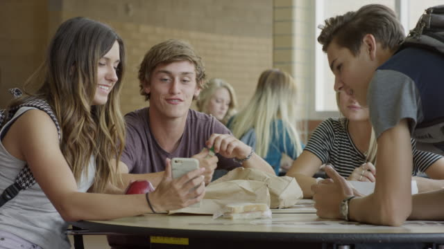 medium shot of students examining cell phone in school cafeteria / mapleton, utah, united states - kantine stock-videos und b-roll-filmmaterial