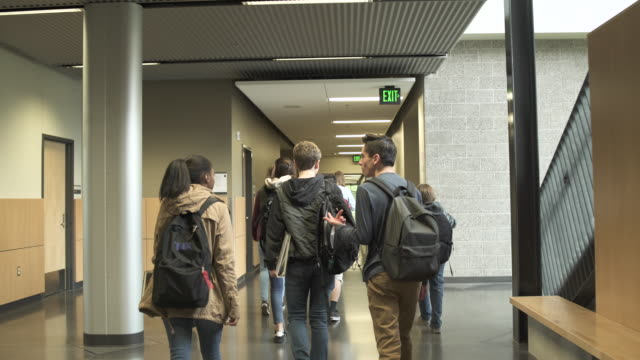 Medium shot of students walking in school corridor
