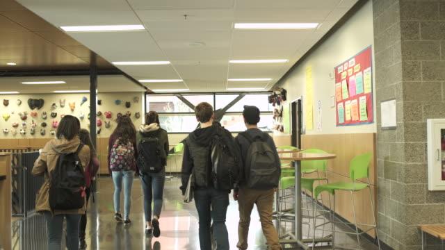 medium shot of students walking in school restaurant - junior high stock-videos und b-roll-filmmaterial