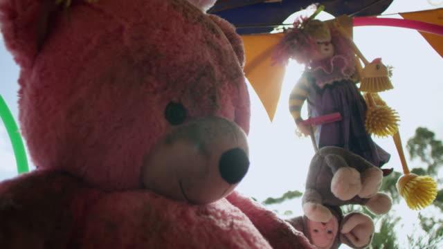 vidéos et rushes de medium shot of stuffed toys hanging in empty theme park - parc d'attractions