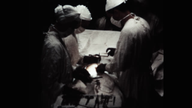 medium shot of surgeons and nurses performing operation in operating theatre - operation stock videos & royalty-free footage