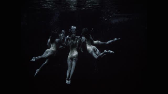 medium shot of synchronized swimming team performing in lake - akrobat stock-videos und b-roll-filmmaterial