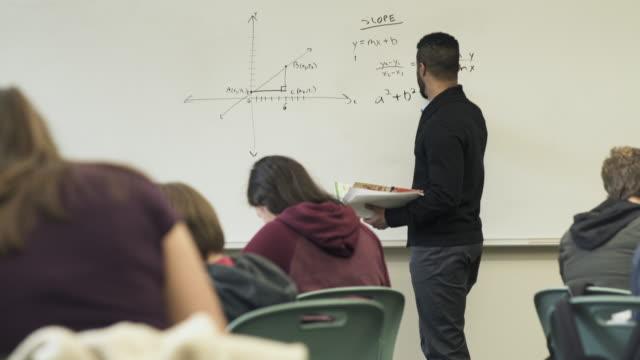 Medium shot of teacher holding math class