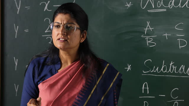 medium shot of teacher scolding while writing mathematical formula on blackboard in classroom - authority stock videos & royalty-free footage