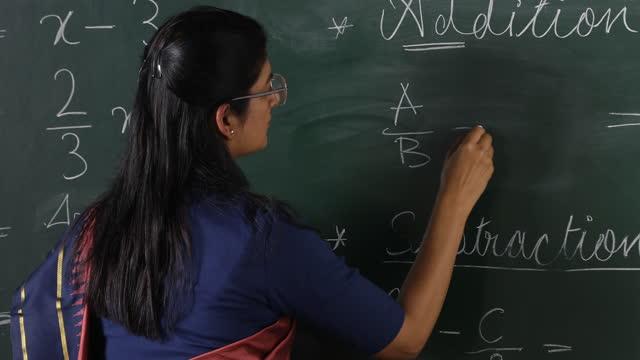 medium shot of teacher scolding while writing mathematical formula on blackboard in classroom - blackboard stock videos & royalty-free footage