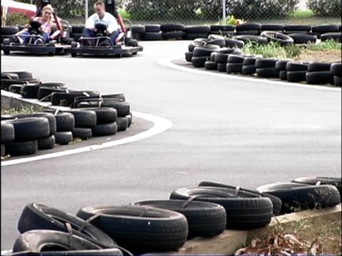 Medium shot of teen boy and girl racing in go-carts on a curvy road track.