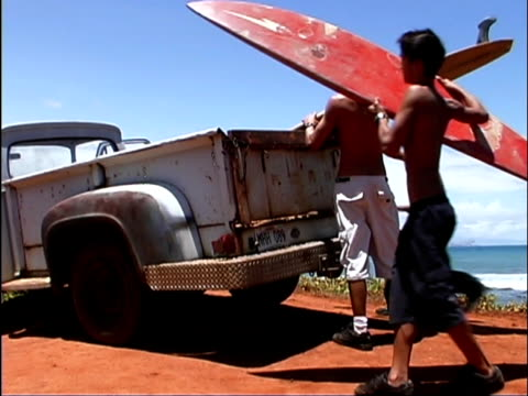 medium shot of teen boys putting surfboards in the back of a pickup truck. - pacific islanders stock videos & royalty-free footage