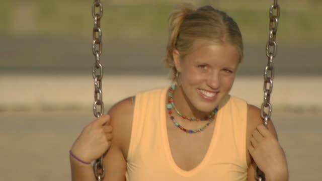 vídeos de stock e filmes b-roll de medium shot of teen girl on a swing - só uma menina adolescente
