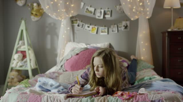 """medium shot of teenage girl doing homework on bed / cedar hills, utah, united states"" - only teenage girls stock videos and b-roll footage"