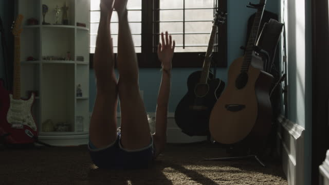 medium shot of teenage girl doing sit-ups in bedroom / sandy, utah, united states - sit ups stock videos & royalty-free footage