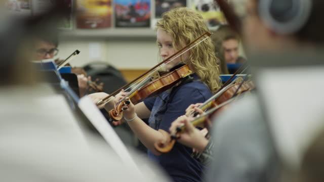 medium shot of teenage girl playing violin in orchestra practice / american fork, utah, united states - violin stock videos & royalty-free footage